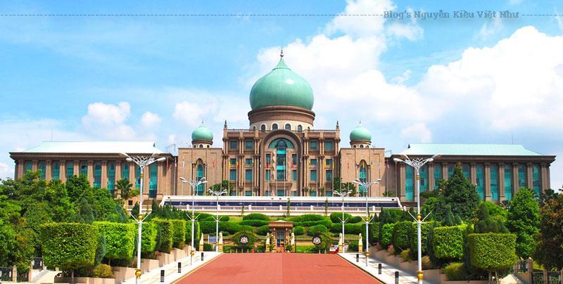 """Được đặt trung tâm thành phố Putrajaya – nơi được xem là """"thành phố vườn"""" của Malaysia, tòa nhà Perdana Putra với 6 tầng rộng lớn lọt thỏm giữa rừng cây xanh mướt xung quanh, ngay bên cạnh là hồ Putrajaya trong lành."""