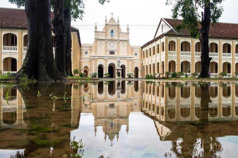 """Tiểu chủng viện Làng Sông là một công trình kiến trúc theo phong cách Gotic đẹp với đặc trưng tháp """"bút chì"""" cao vút, hành lang với cổng vòm cuốn thanh thoát, nhiều cột vuông."""